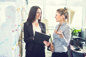 Two businesswomen talking to each other in the office.